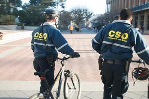 Two CSOs in blue jackets with police radios walking bikes